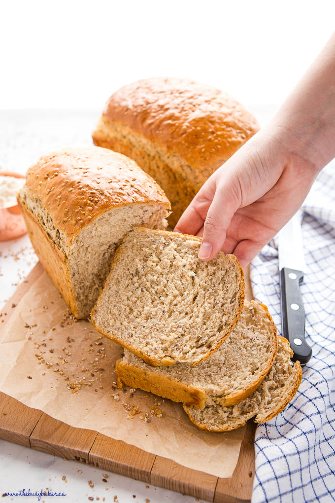 hand reaching for slice of whole grain bread