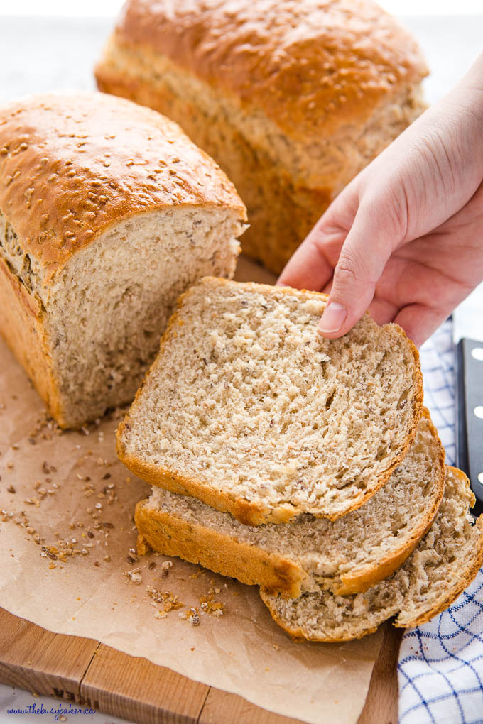 hand reaching for a slice of whole grain bread