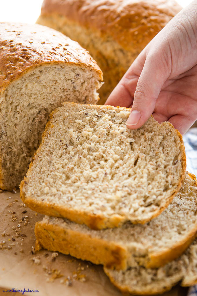 closeup image: hand reaching for a slice of whole grain bread