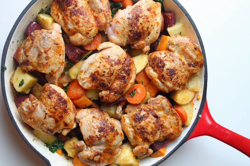 paprika chicken thighs in a pan with carrots and potatoes