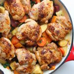 paprika chicken thighs in a pan with roasted root vegetables