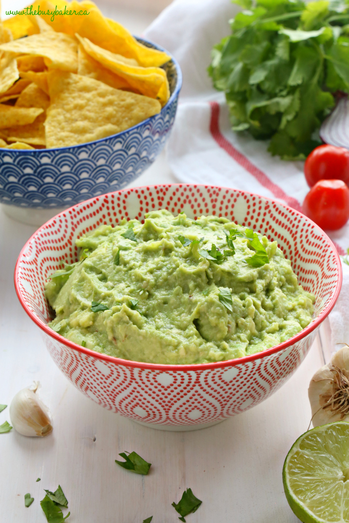 Best Ever Healthy Guacamole in Red and White Bowl with chips