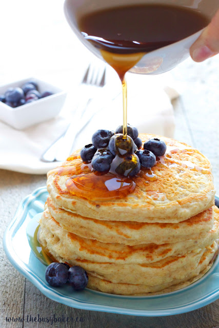 pouring maple syrup onto a stack of homemade buttermilk pancakes