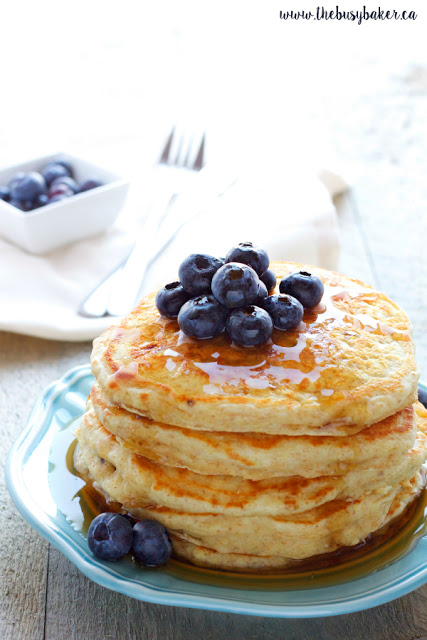 stack of buttermilk pancakes with maple syrup and fresh blueberries