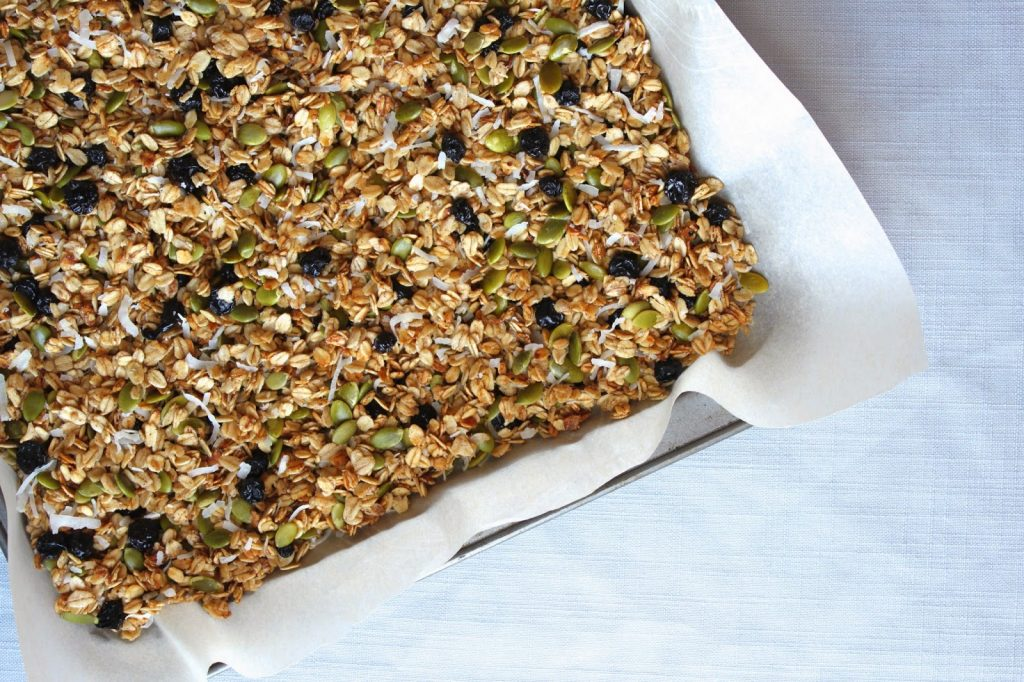 pumpkin seed granola with blueberries on a baking sheet