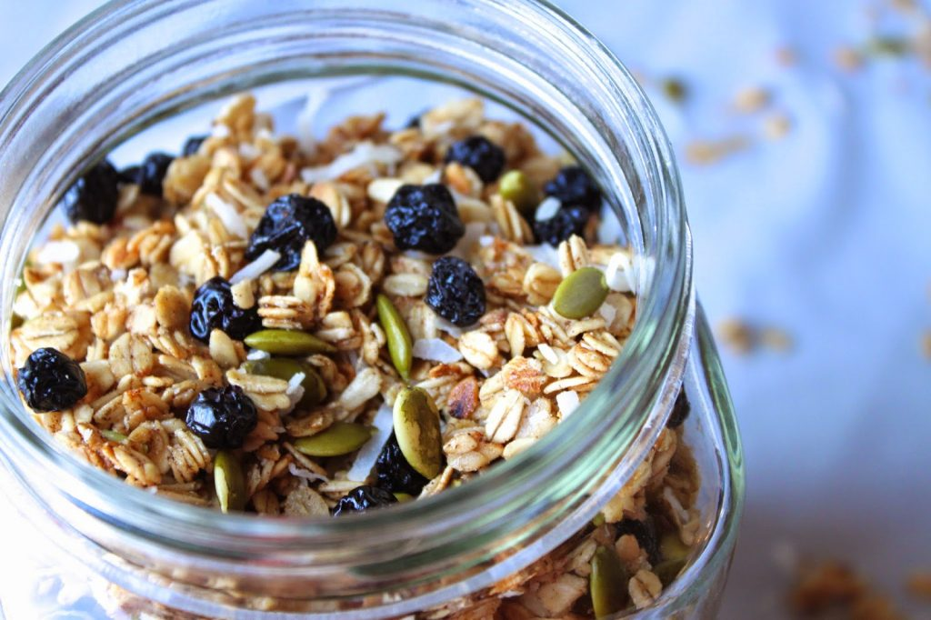 jar of homemade granola with pumpkin seeds and dried blueberries