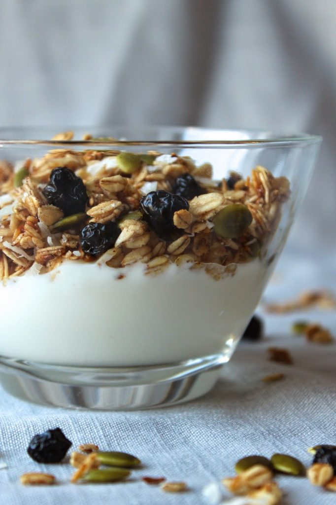 bowl of pumpkin seed granola with fresh blueberries and milk