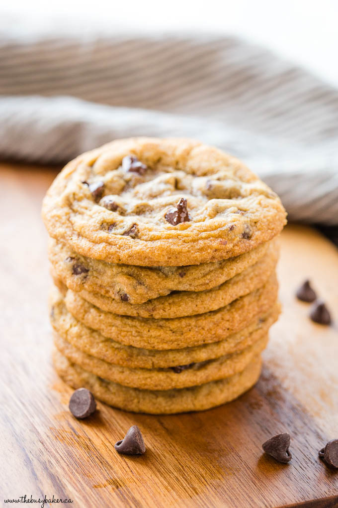 stack of chocolate chip cookies on a wooden cutting board