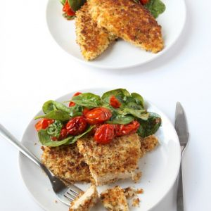 plated dinner of chicken Milanese with roasted tomatoes and spinach