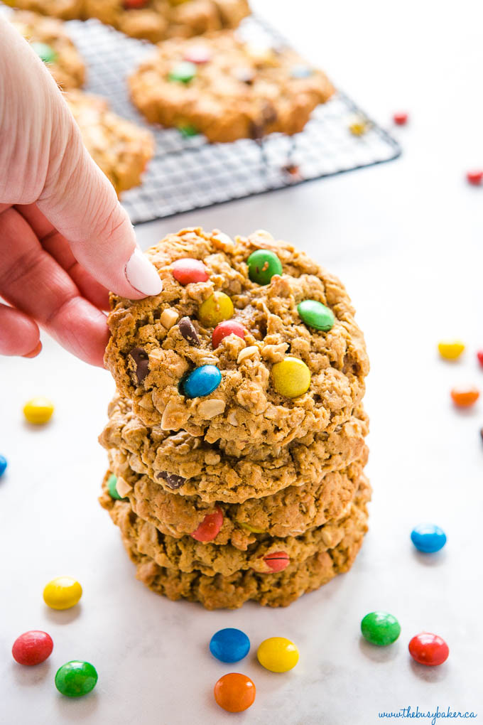 hand reaching for a monster cookie with m&ms