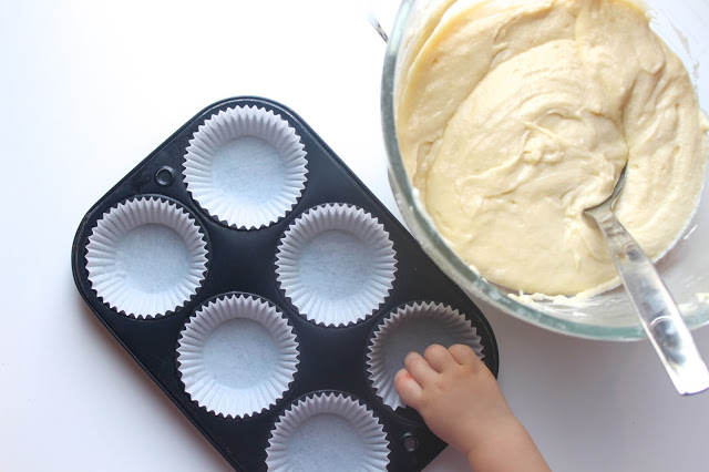 cupcake pan lined with paper cupcake liners next to a bowl of cupcake batter