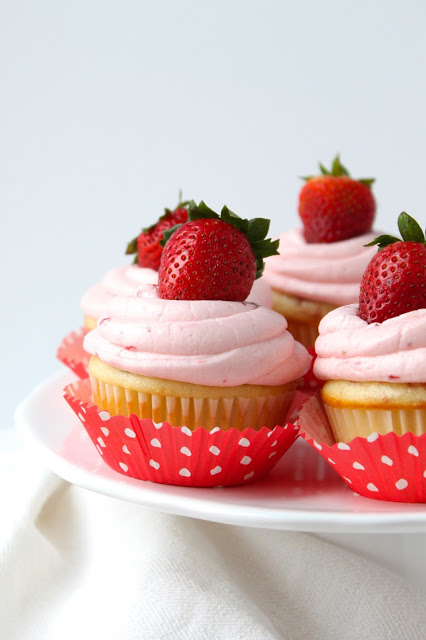 cake plate holding homemade strawberry cupcakes topped with strawberry buttercream and whole fresh strawberries