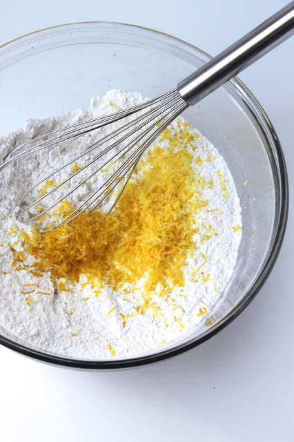 whisking lemon zest into a bowl with white flour and sugar