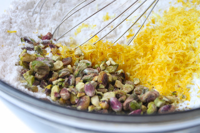 whisking lemon zest and chopped pistachios into a bowl with flour