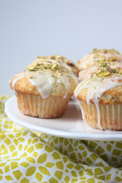 pistachio muffins topped with powdered sugar glaze and crushed pistachios