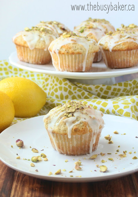 a white platter holding lemon pistachio muffins topped with cream cheese glaze and crushed pistachios