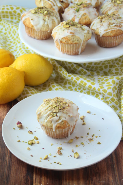 moist lemon muffins topped with chopped pistachios and sweet lemon glaze