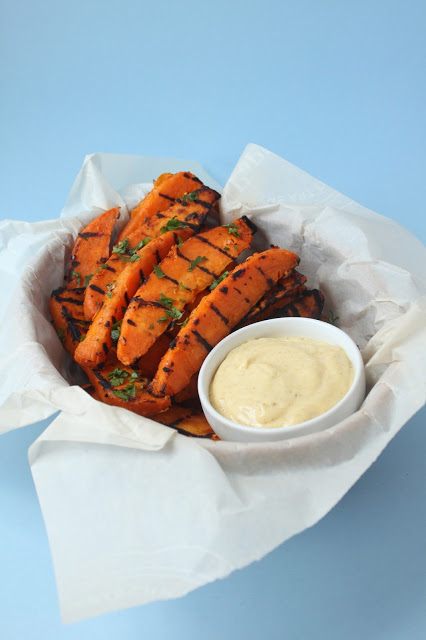 parchment paper lined basket of grilled sweet potatoes wedges
