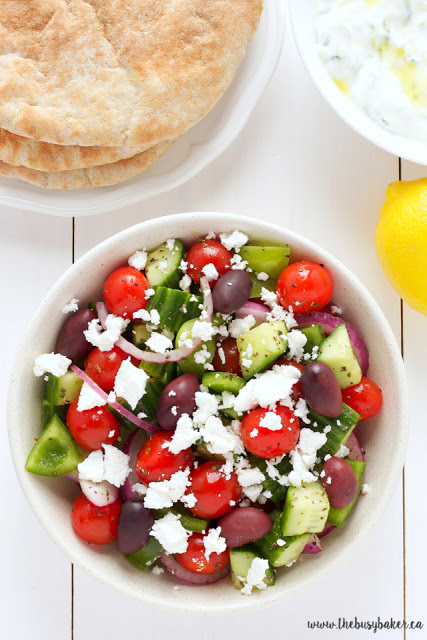 simple Greek salad with fresh pita on a plate next to it