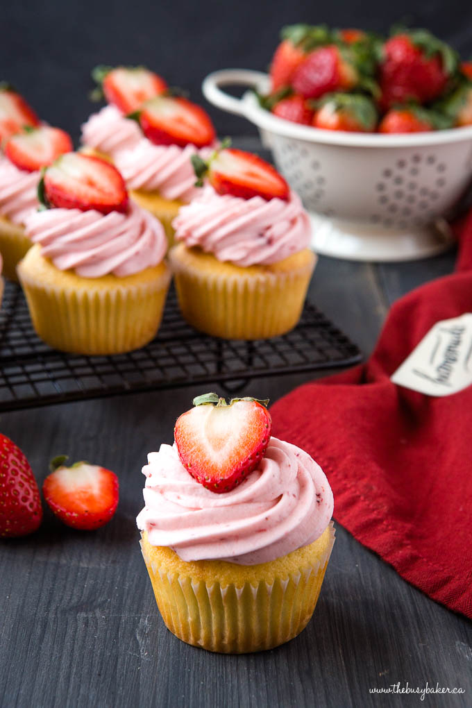 strawberry cupcakes with fresh strawberry buttercream frosting and half a strawberry on top
