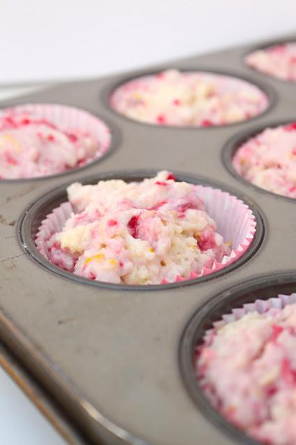 raspberry lemonade muffin batter in a muffin pan