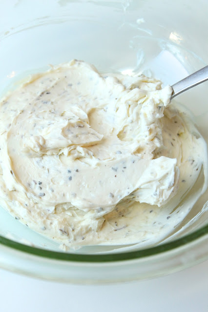 cream cheesei, garlic and herbs being combined in a bowl