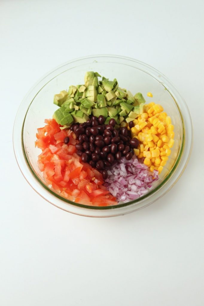 glass bowl with corn, avocado, tomato, black beans, and red onion