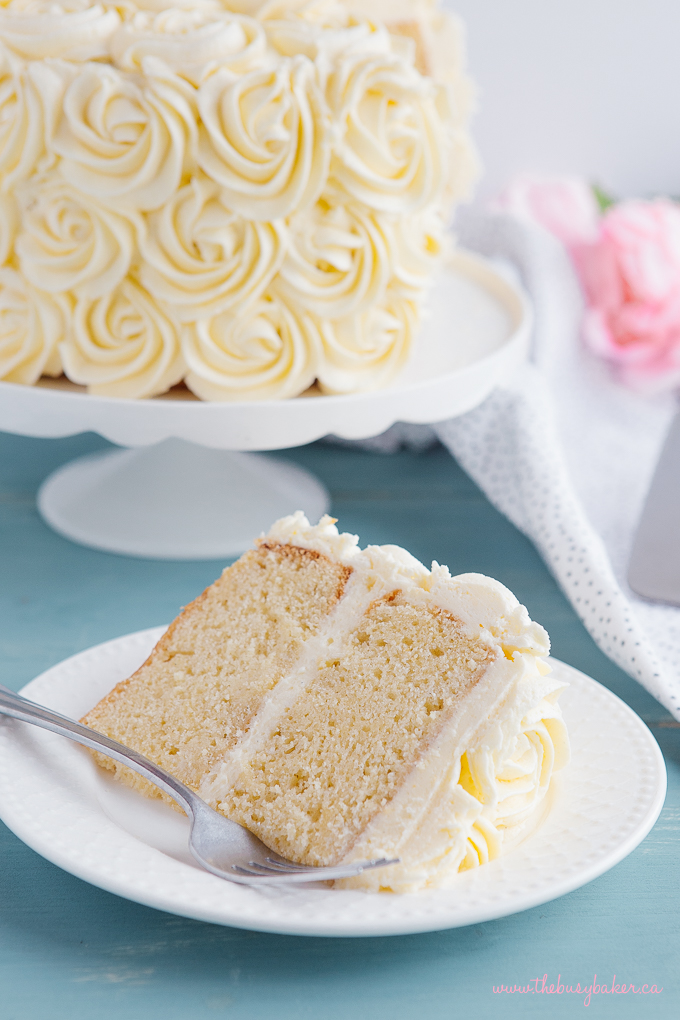 Best Ever Vanilla Bean White Cake Slice On Plate With Fork And Flowers