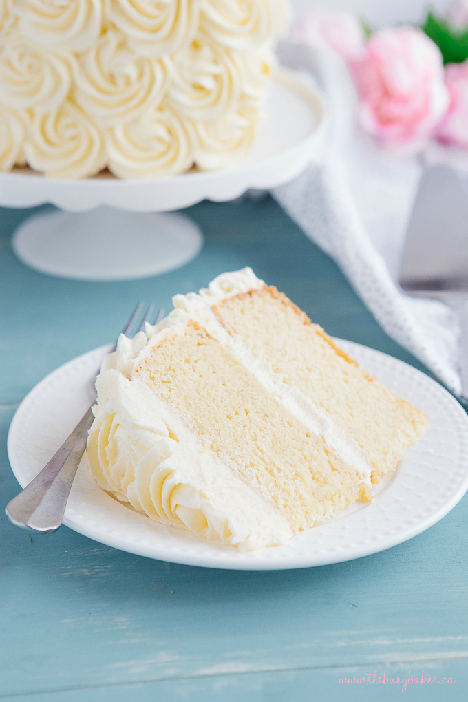 Best Ever Vanilla Bean White Cake slice on white plate with fork