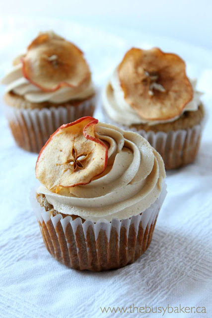 apple caramel cupcakes garnished with caramel frosting and homemade apple chips