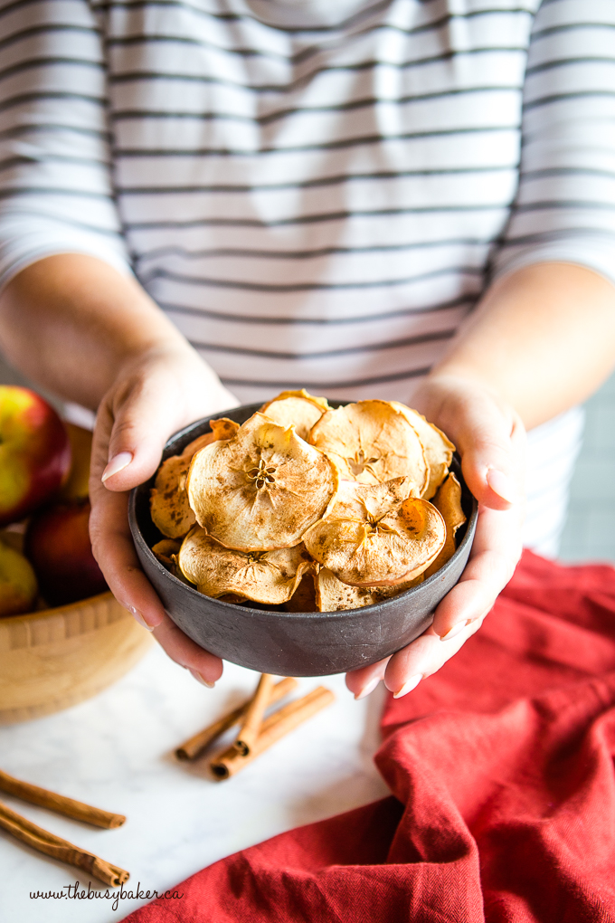 apple chips in black bowl in woman's hands