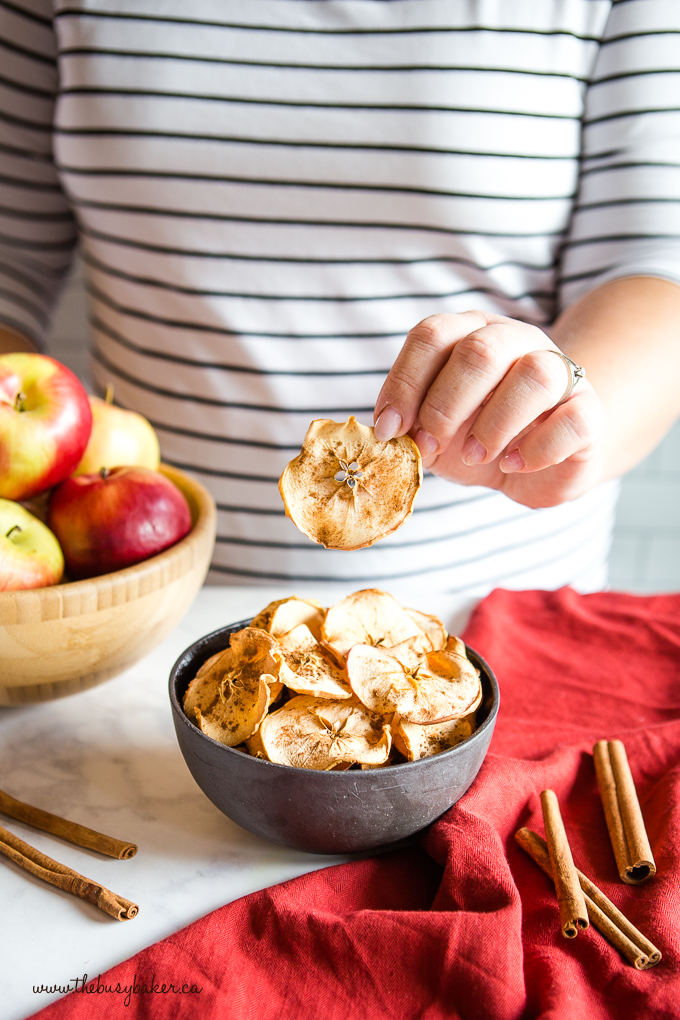 Apple Chips in black bowl in woman's hand