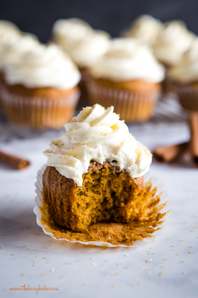 bite out of pumpkin spice cupcake with cream cheese frosting