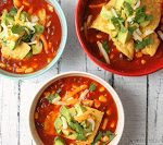 bowls of Mexican tortilla soup topped with avocado, shredded cheese and tortilla chips