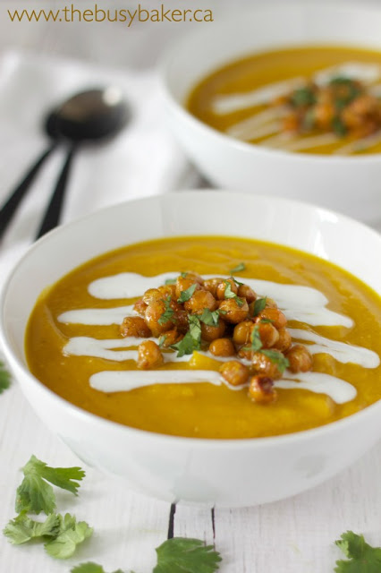 a bowl of vegan butternut squash soup garnished with coconut cream and dry roasted chickpeas