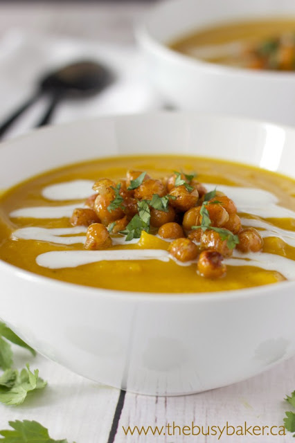 bowl of butternut squash red lentil soup topped with roasted chickpeas and coconut cream