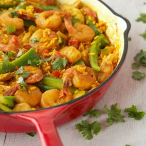 red cast iron skillet filled with chicken and shrimp paella
