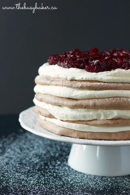 meringue torte cake layered with whipped cream and cranberries