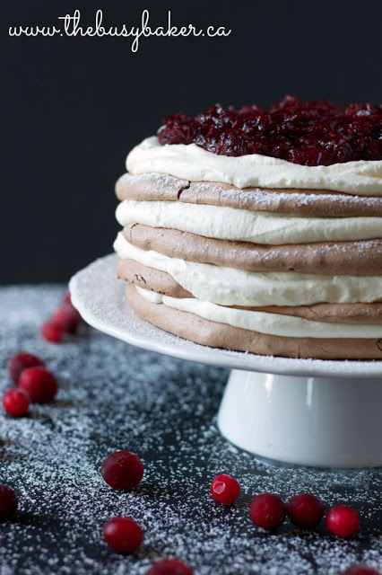 layered meringue pavlova dessert topped with cranberry compote