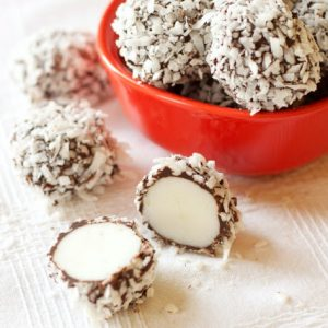 red bowl filled with peppermint chocolate snowball truffles. One truffle, sliced in half, sits in front of the bowl