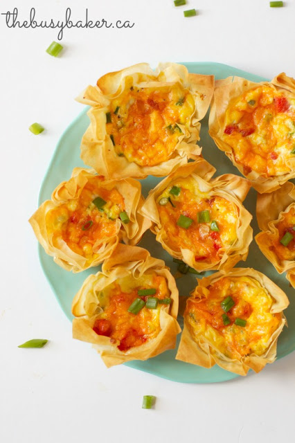 a green platter of roasted red pepper quiche cups appetizers
