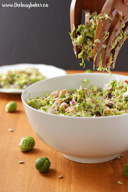 healthy Brussels sprouts salad in a white bowl, being tossed with wooden salad forks