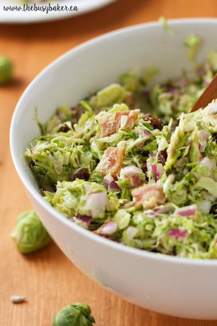 an easy side dish of raw Brussels sprouts, red onion, bacon, and raisins served in a white bowl