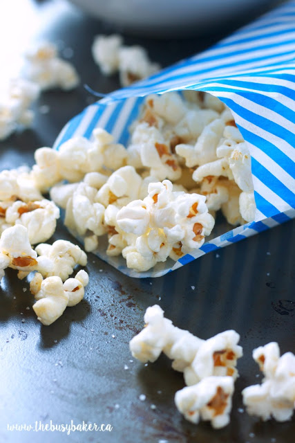 close up image of sweet kettle corn in a blue and white pin striped paper bag