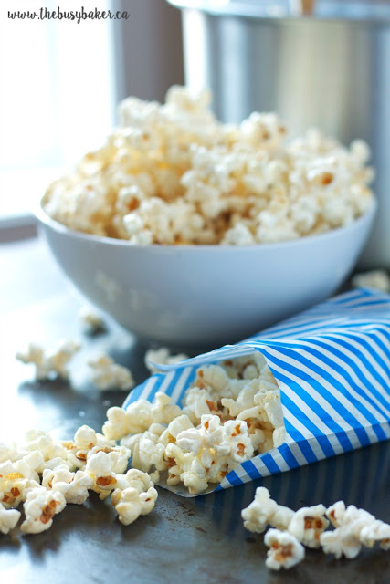blue and white striped paper bags and a bowl, all filled with a homemade kettle corn recipe