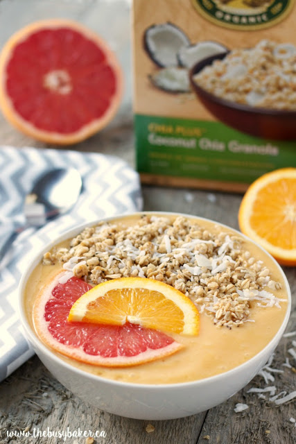 mango smoothie bowl with banana, citrus fruits, coconut and granola on top