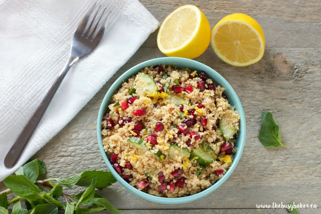 a fork and lemon wedges next to a bow of lemon couscous salad with pomegranate arils and fresh mint