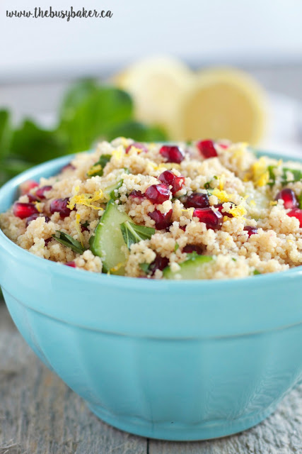 light blue bowl of fluffy whole wheat couscous salad with pomegranate arils, lemon, and mint