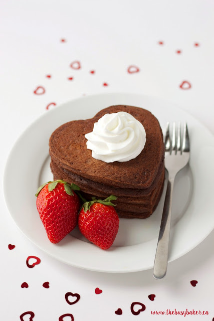 a plate of chocolate heart shaped pancakes with fresh strawberries and whipped cream