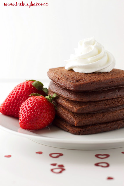 stack of chocolate heart-shaped buttermilk pancakes topped with whipped cream